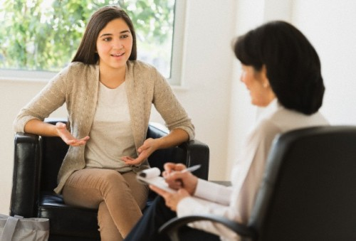 Teenage girl (16-17) talking to therapist --- Image by © Tetra Images/Corbis
